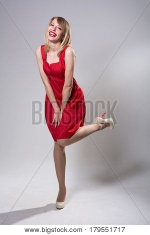 Young Smiling Woman Standing On One Leg In A Red Dress.