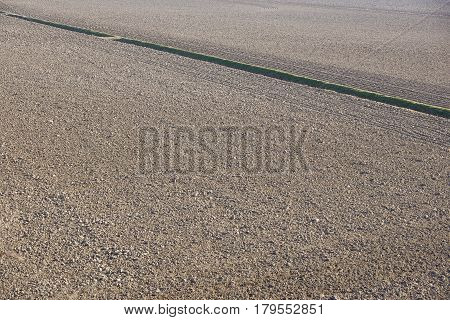 Top Aerial view of furrows row pattern in a plowed field prepared for planting crops in spring.