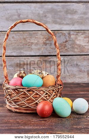 Chicken and quail eggs, basket. Easter basket, brown wooden background. How to dye eggs.