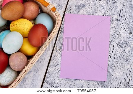 Easter egg basket, empty card. Blank paper, wooden background. Easter party invitation template.