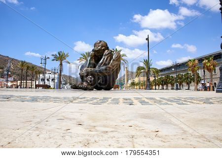 The huge iron manCartagena, Spain - July 13, 2016: Monument El Zulo, created by sculptor Victor Ochoa. Dedicated to the victims of terror in Madrid in 2004
