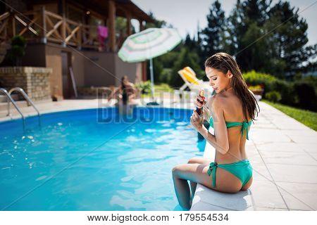 Beautiful woman applying uv protection lotion at summer