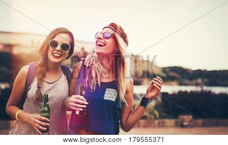 Happy friends laughing and having fun outdoors at concert