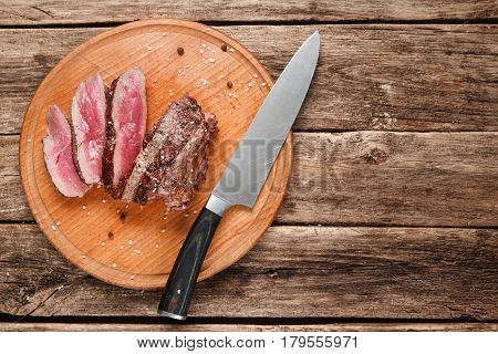 American junk food. Slices of superior grilled beef steak served on round platter with knife, on rustic wooden table with copy space for text. Top view.