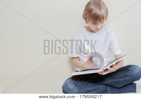 Little kid reading a book. Education, school, leisure concept