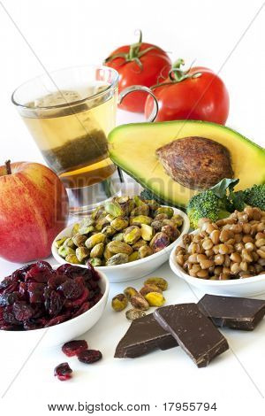 Foods rich in antioxidants, over white background.  Includes cranberries, apple, green tea, tomatoes, broccoli, avocado, lentils, pistachios and dark chocolate.