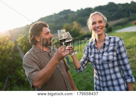 Wine growers toasting with red wine in wine growers vineyard