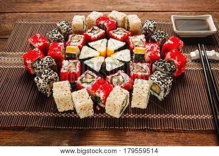 Food art, culinary masterpiece. Great set of sushi served in colorful ornament on brown straw mat, closeup. Luxury restaurant menu photo.