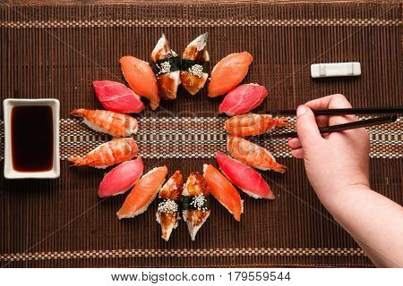 Great tasty set of colorful nigiri sushi served in round form on brown straw mat, flat lay. Unrecognizable hand take piece with chopsticks. Japanese cuisine.