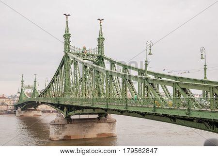BUDAPEST HUNGARY - FEBRUARY 21 2016: Liberty Bridge or Freedom Bridge in Budapest Hungary connects Buda and Pest across the River Danube.
