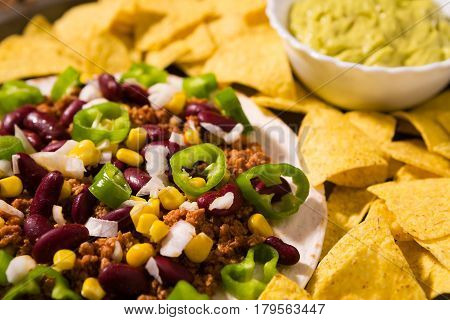 Closeup of Mexican tortillas with meat red beans Jalapeno pepper and nachos chips over an old wooden table