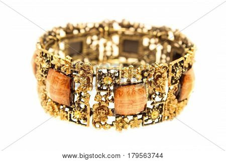 Beautiful bracelet made of yellow metal with square stones isolated on white background.