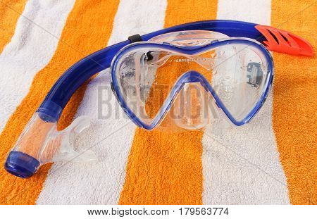 Mask and snorkel diving lying on a towel.
