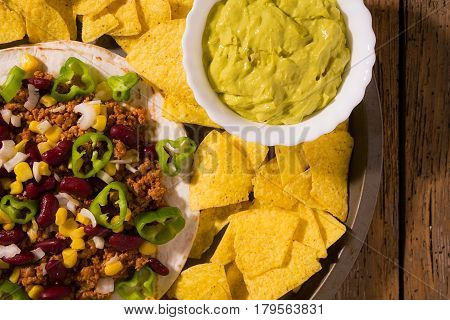 Mexican tortillas with meat red beans Jalapeno pepper nachos chips and salsa guacamole seen from above