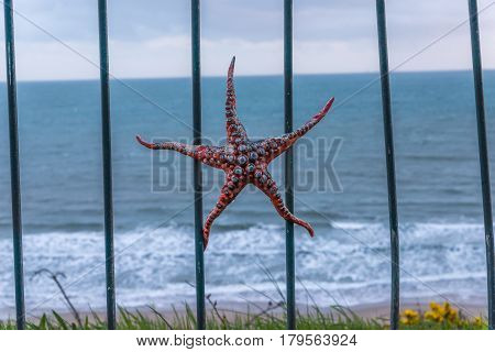 Metal Ornament On A Balustrade In A Coastal Town, A Symbolic Starfish-shaped Element