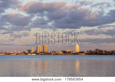 City residential and industrial buidings glowing golden in a vibrant sunset across reflecting waters