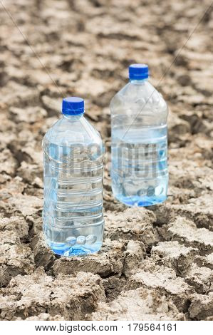 Bottle with water on the dried ground. Concept of Global drought, warming. Dried soil. lack of water, thirst concept.