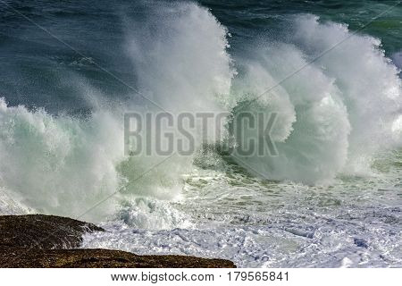Wave crashing against rocks during storm day