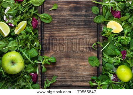 Green food background. Salad ingredients on table with copy space and cutting board for your text. Healthy food and diet concept.