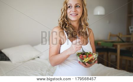 Beautiful pregnant woman eating healthy food and salads