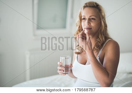 Beautiful pregnant woman taking pills for morning nausea