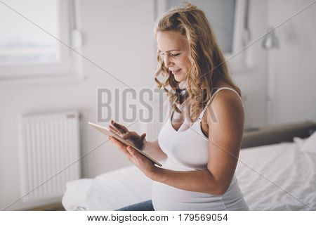 Beautiful expectant pregnant woman using tablet and smiling