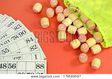 top view of details of Russian vintage game Bingo or Lotto with white paper cards in the cells are written black numbers small wooden barrels which read pink numbers green bag on the table red color