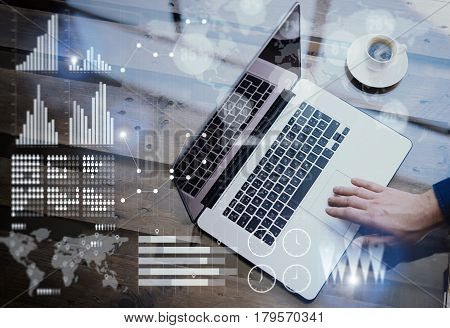 Concept of digital diagram, graph interfaces, virtual screen, connections icon.Businessman working at office on laptop at the wooden table.Male hand touching mobile computer touch pad.Blurred background