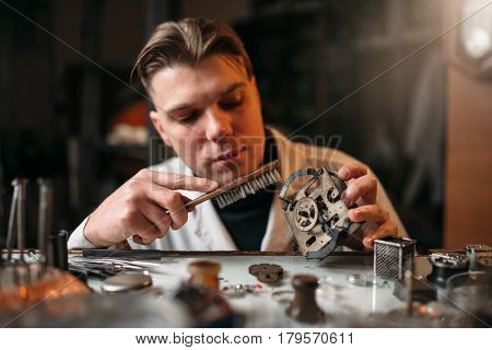 Watchmaker cleans the mechanism of old watches