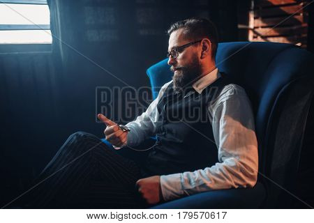 Man sitting in armchair, looking at pocket watch