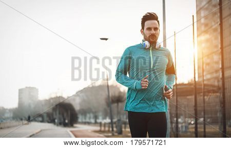 Handsome runner exercising by running and jogging in city