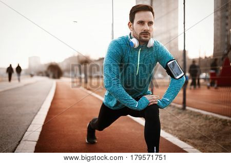 Handsome man stretching before exercising and running