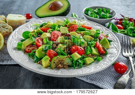 Quinoa tabbouleh salad with avocado, tomatoes, cucumber, green onion. Concept healthy food