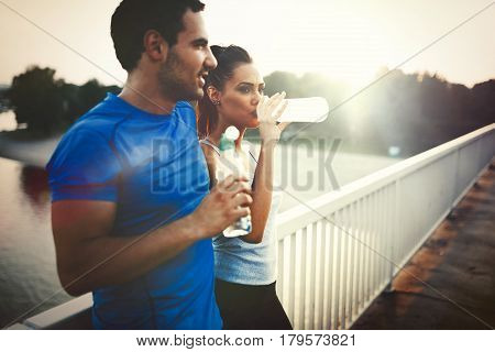 Couple drinks water to replenish energy and to hydrate after jogging