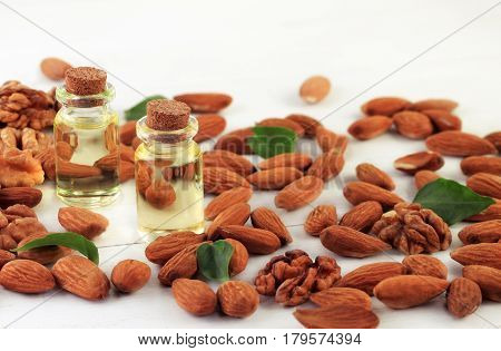 Almond nuts scattered white wooden table, bottles of culinary and cosmetic skincare seed oil.