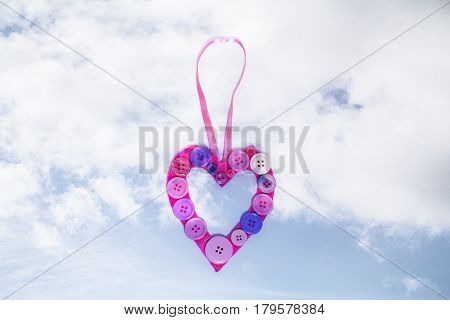 A handmade button heart full of crafty love hanging in the clouds