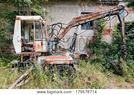Old deserted and broken digger overgrown with grass