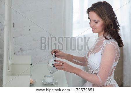 Beautiful woman in the morning in the bedroom drinking a morning tea.