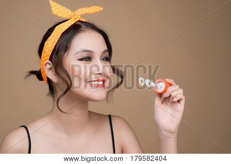 Playful Pinup Woman Blowing Party Bubbles Over Yellow Background