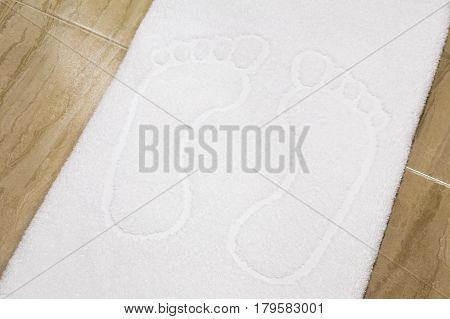 Pair of human footprint outline embossed on soft white hotel bath towel over hard floor