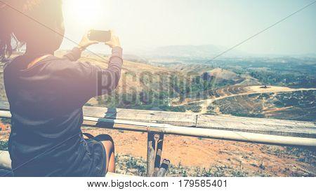 Woman hand using mobile phone photo. Mountain nature