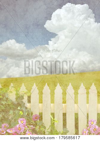 White picket fence with ivy and pink flowers in front of a green grassy hill and blue sky cloudscape background. Vintage paper textured image.
