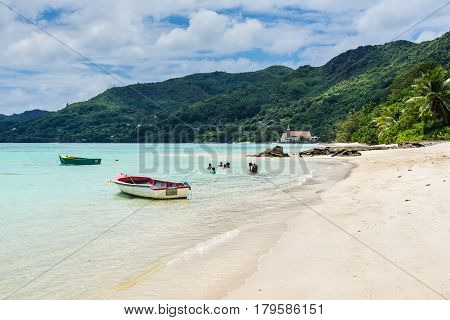 Anse Royale Mahe Island Seychelles - December 15 2015: Seychelles paradise the Anse Royale beach of Mahe with white sand turquoise sea and coconut trees. Some people enjoying the Beach Mahe Island Seychelles.