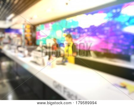 Blurred Image Of Woman And Cashier At The Cash Machine With Shop Background.