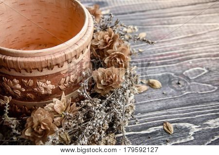 Decoration from dry plants on a wooden background. Ikebana and wattled bowl