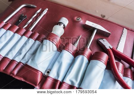 a small hammer, a screwdriver, nippers , saw and fixing pen in red in old vintage leather case right side view. Man's tricks concept