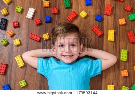 Little Caucasian Child Playing With Lots Of Colorful Plastic Blocks Indoor. Kid Boy Wearing Shirt An