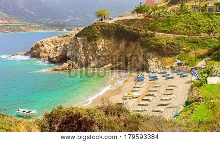 Sandy Evita and Karavostasi beach in sea bay of resort village Bali. Views of shore washed by waves and sun loungers with parasols where sunbathing tourists. Bali Rethymno Crete Greece