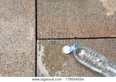 Spilled water with bottle on brick background