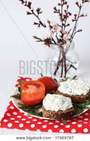 Cheese snack, tomato and a bunch of blooming cherry branches